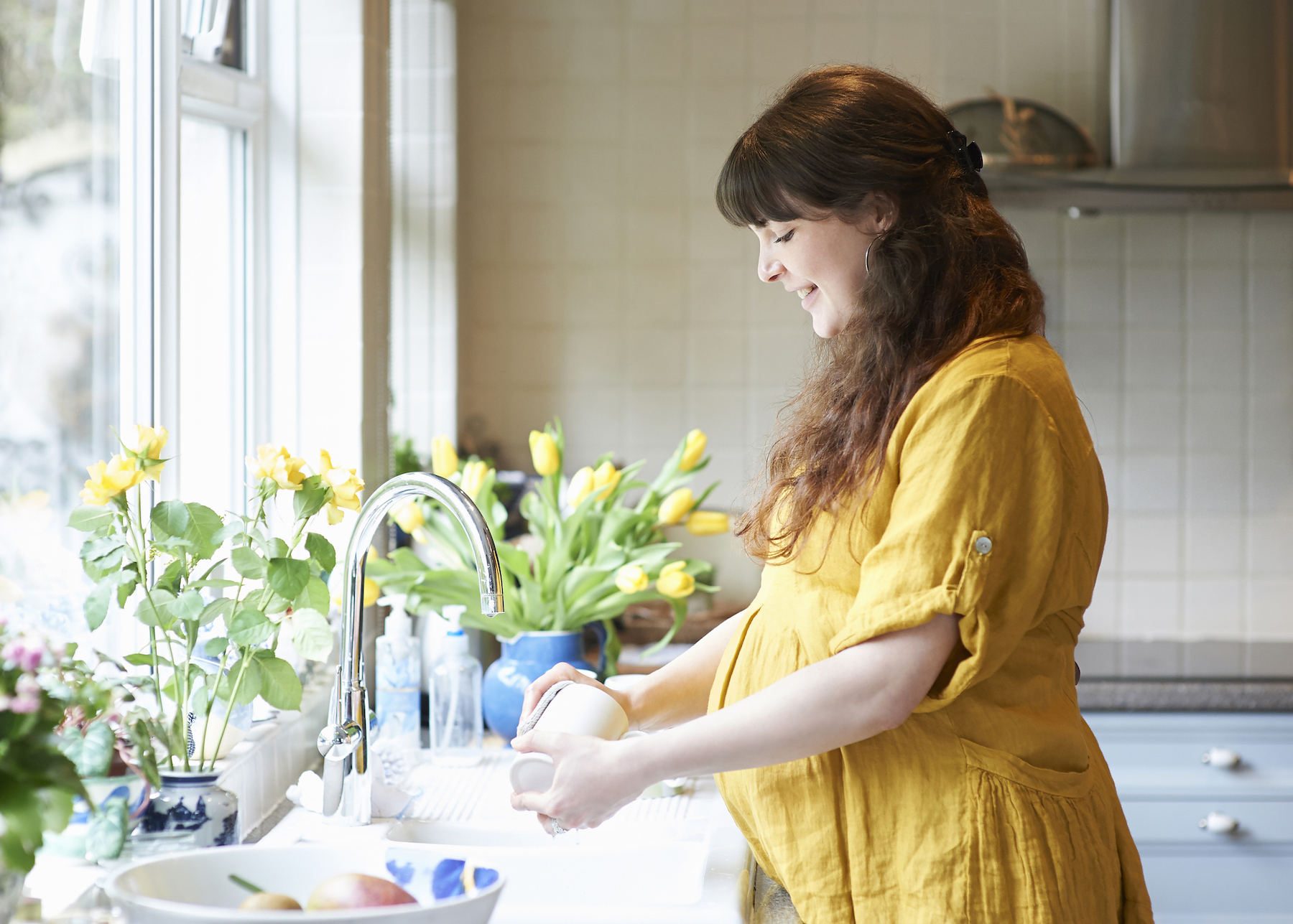 Pregnant Woman Washing Dishes in kitchen