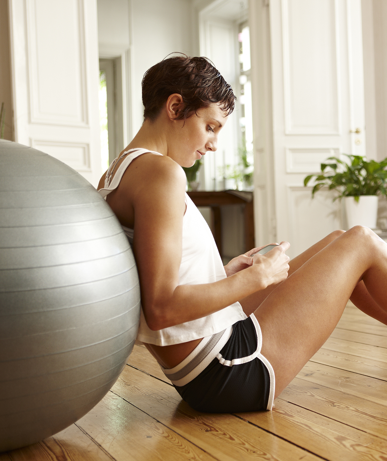 Woman with phone and exercise ball
