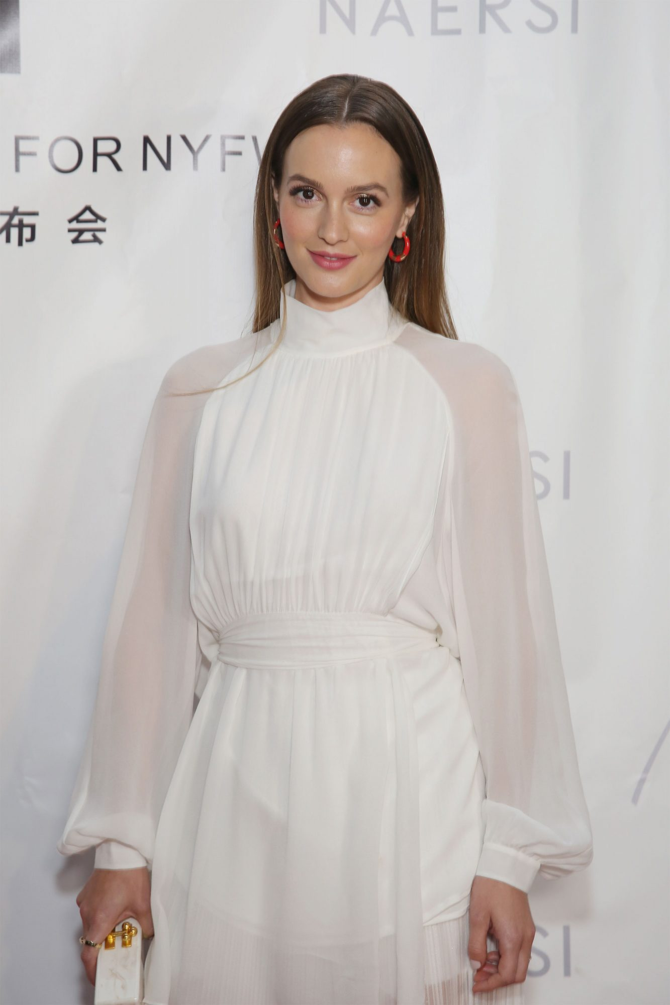 Leighton Mester on a red carpet wearing a white dress