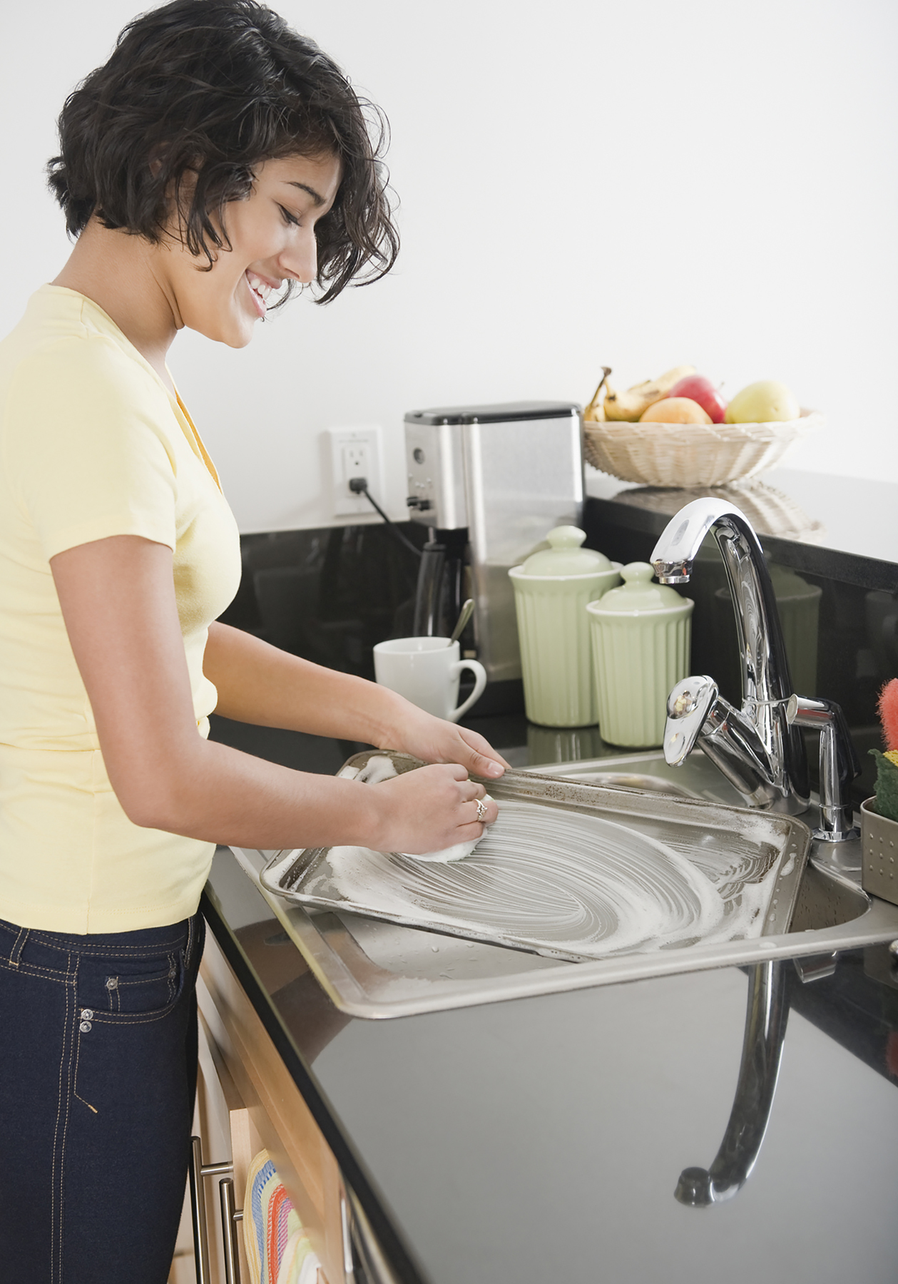 Latina woman washing dishes at sink