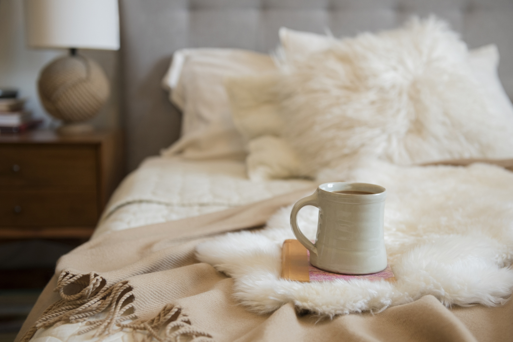 Warm Winter Bed with fur throw blanket and cup of tea