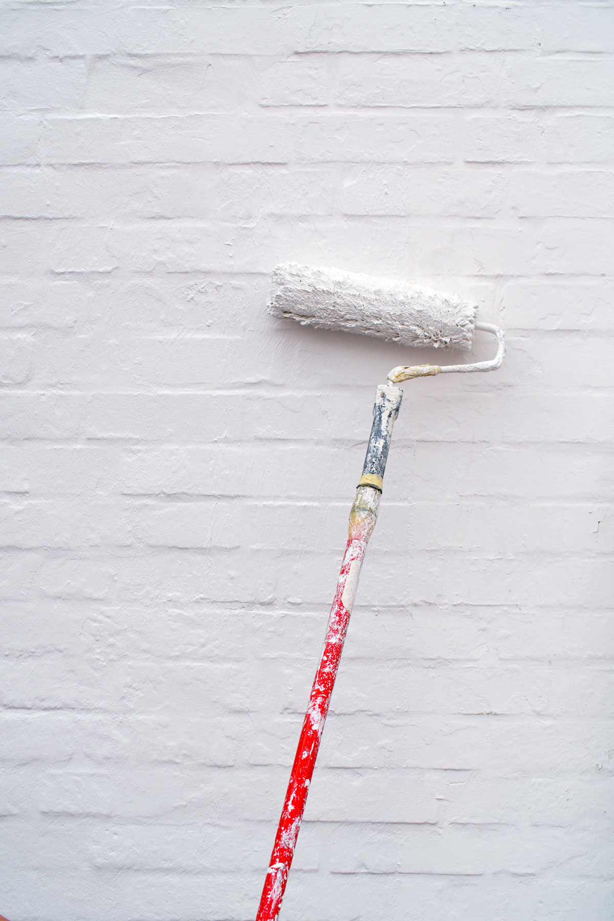 Painting exterior brick white with a roller