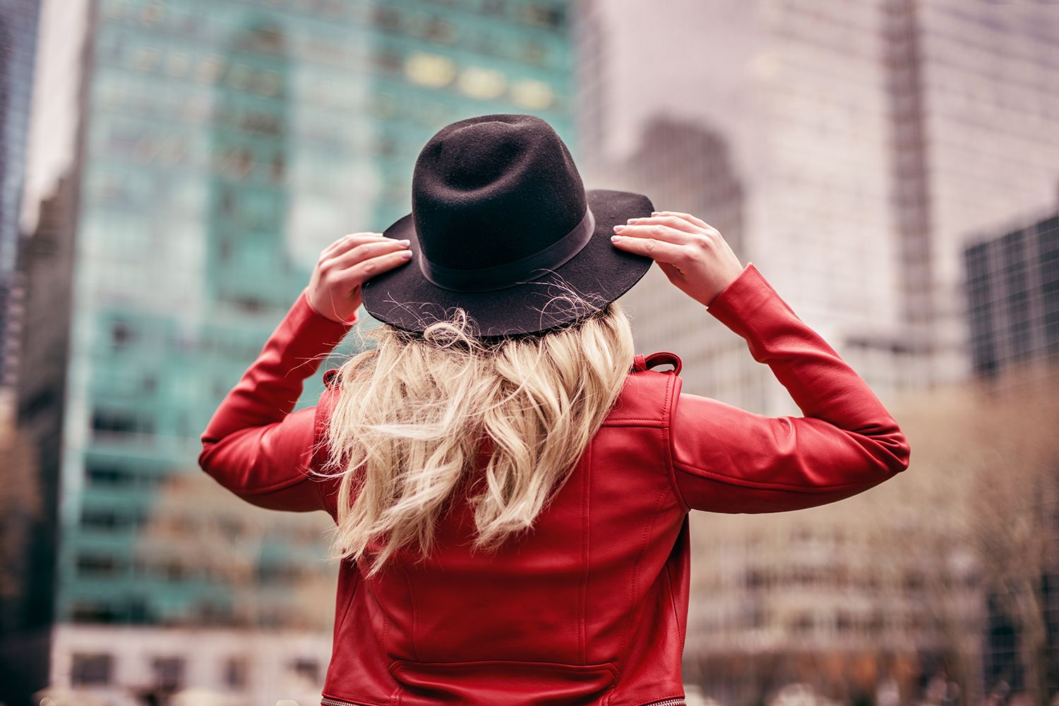 Woman in Red Coat Grabbing Her Hat