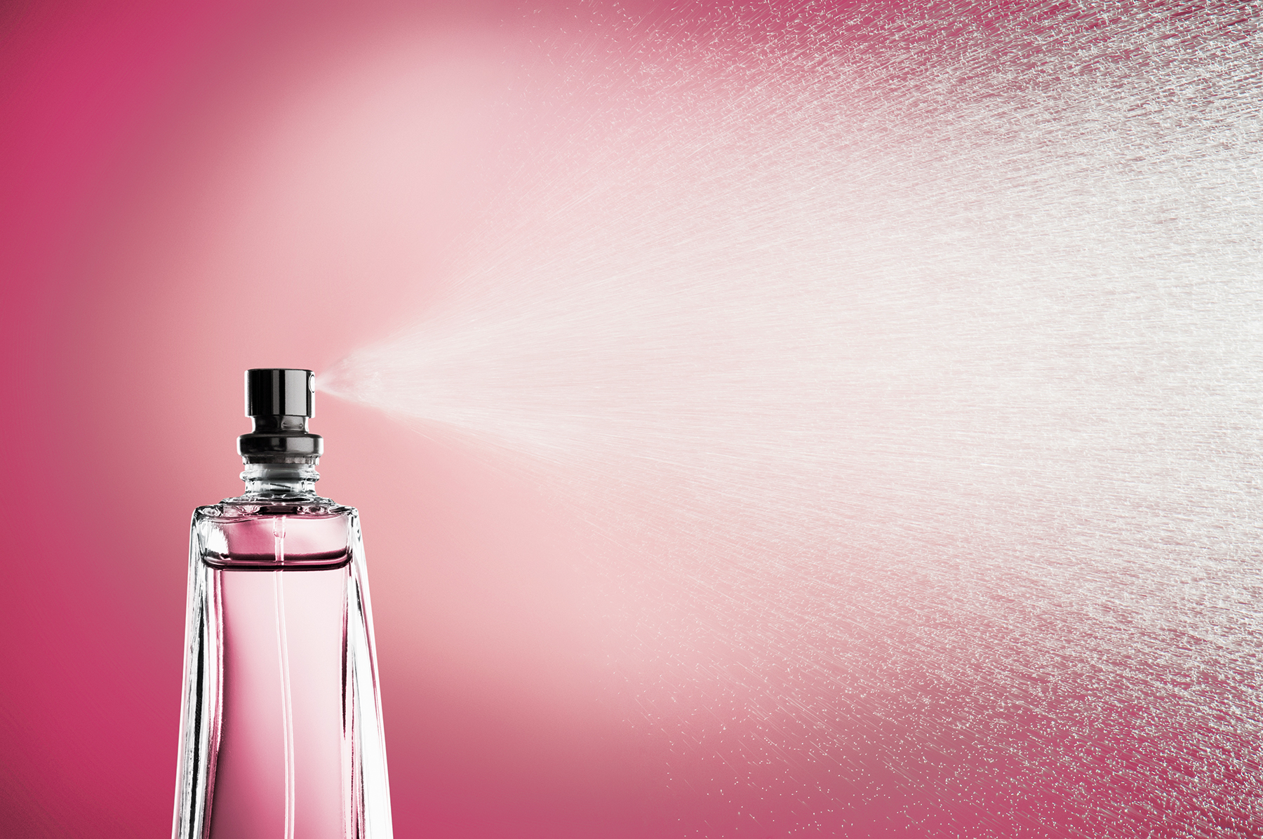 Glass bottle of perfume spraying mist