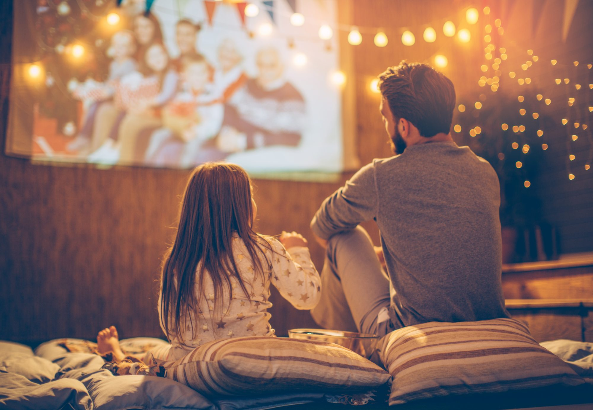 Father and daughter watching an outdoor movie