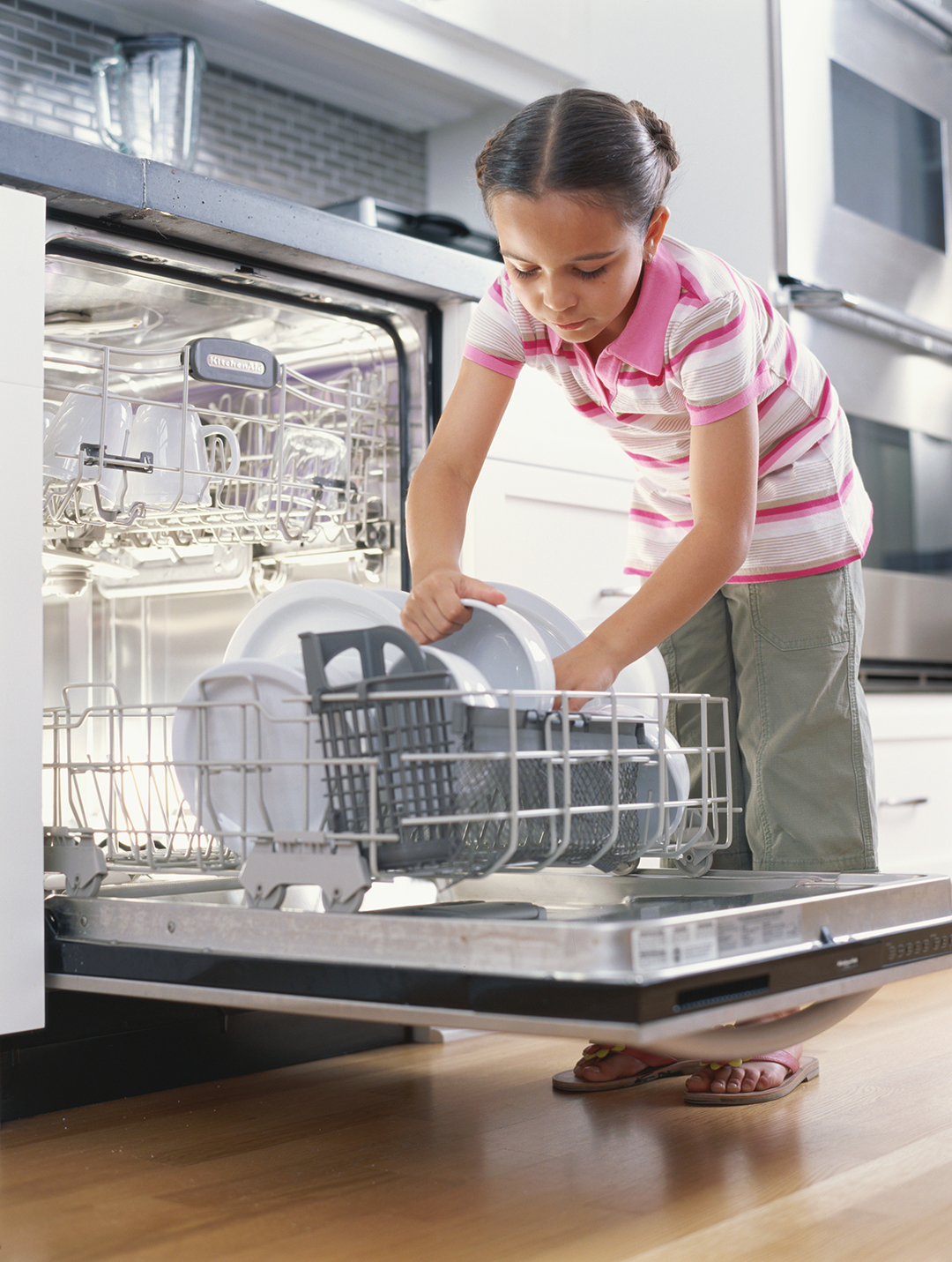 girl loading dishes into dishwasher