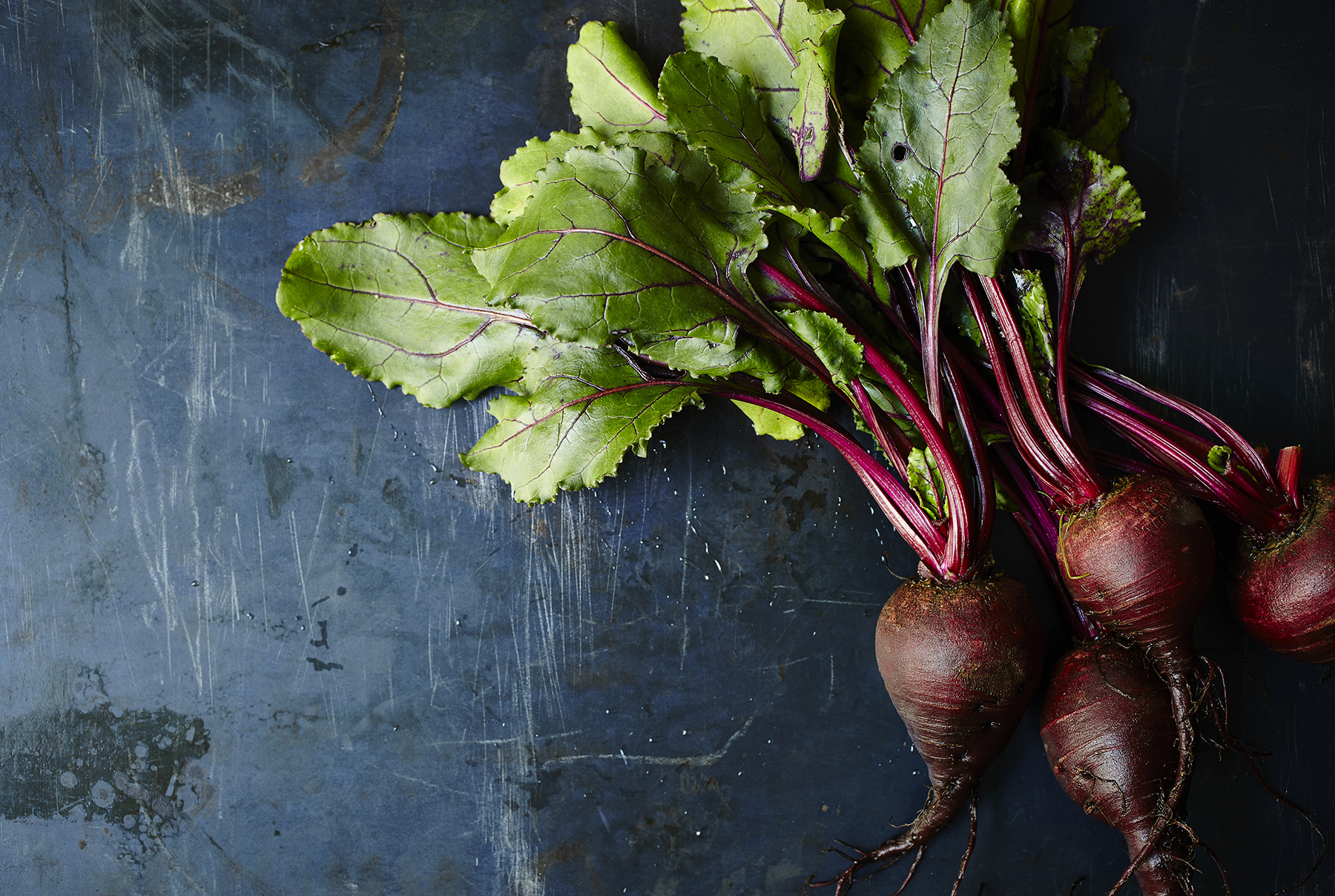 Bunch of fresh beets on blue background