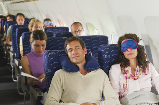 People Sleeping on a Plane to Prevent Jet Lag Symptoms