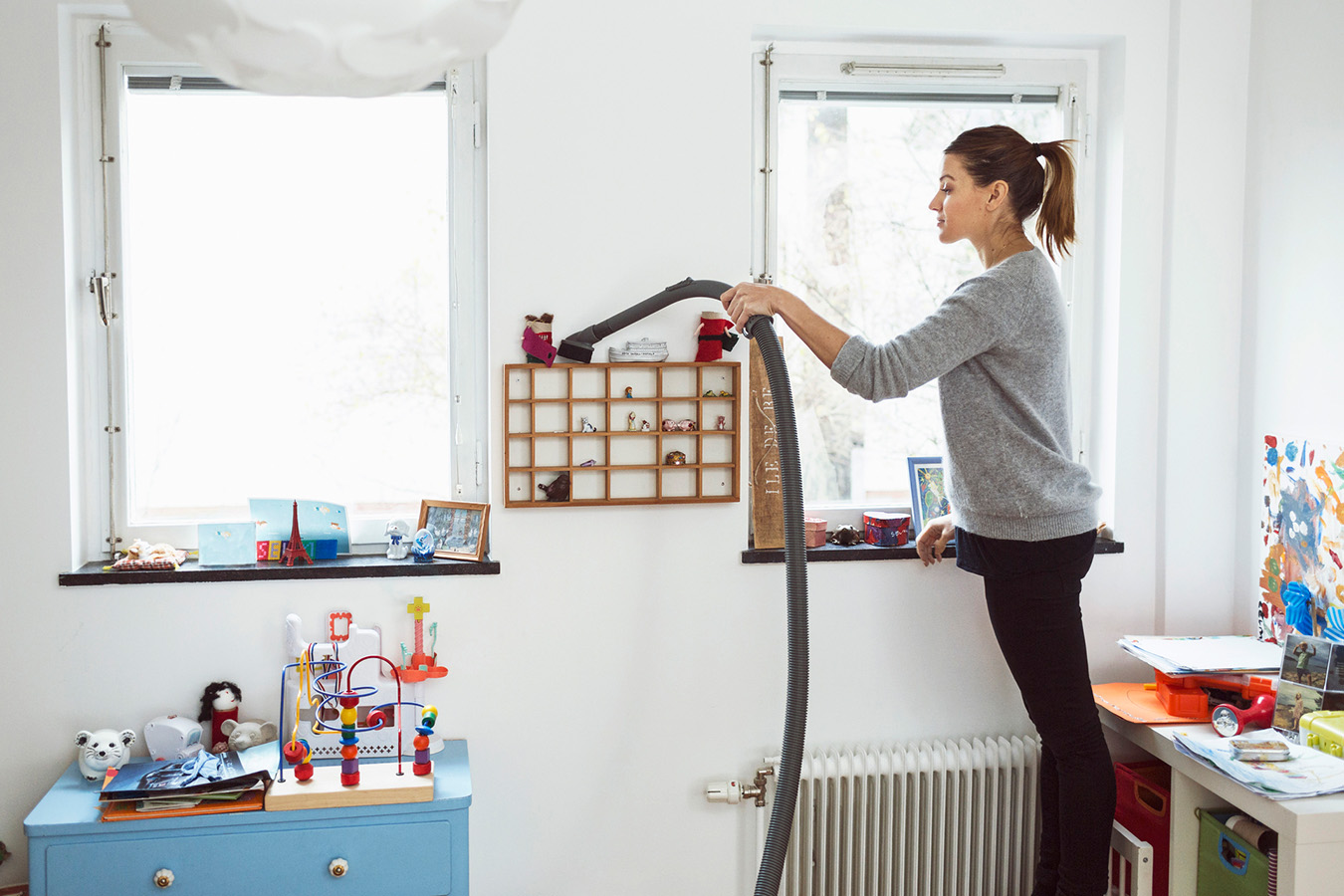 Woman dusting a shelf in a child's room.