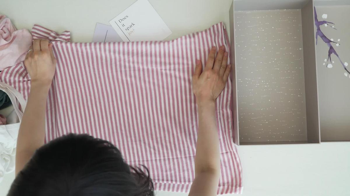 Marie Kondo Folding t-shirt on table