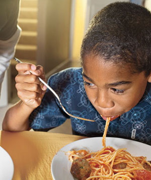 Child eating spaghetti and meatballs