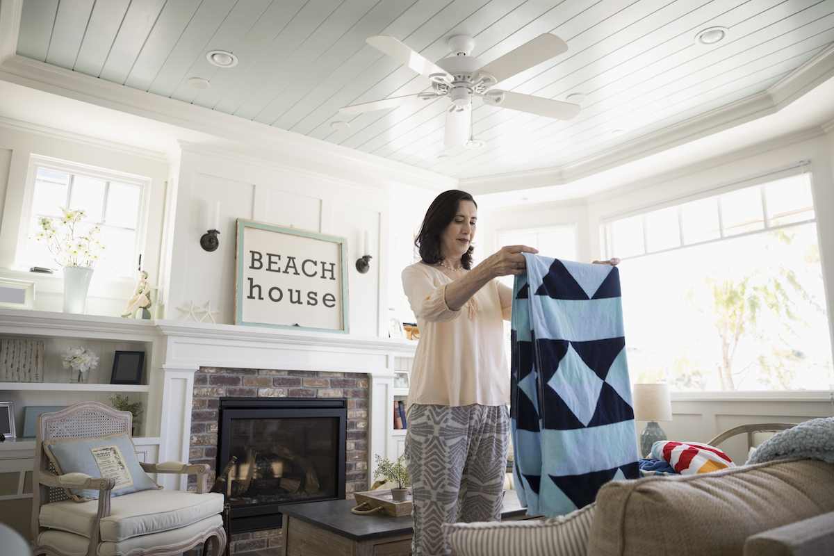 Time-Saving Cleaning Ideas, woman folding blanket in living room