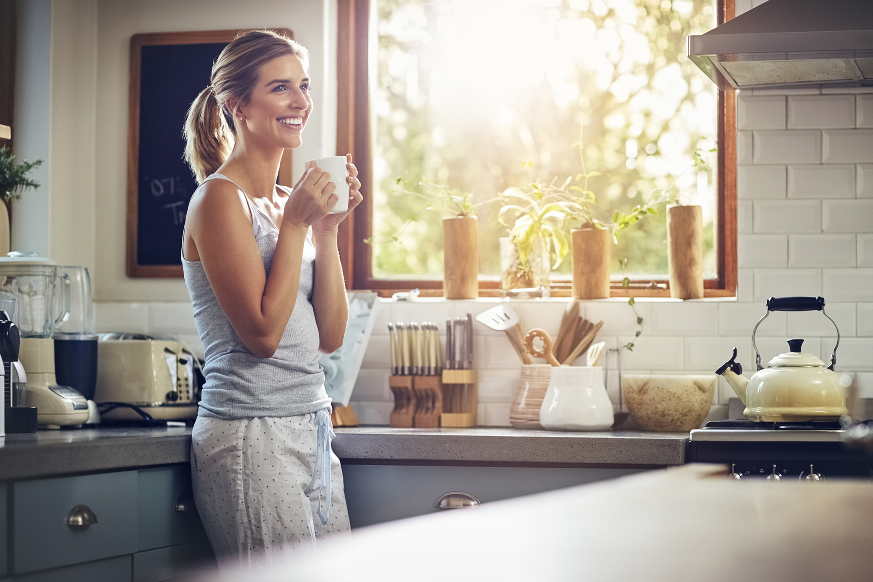 Woman drinking coffee in quiet kitchen with noise-free appliances