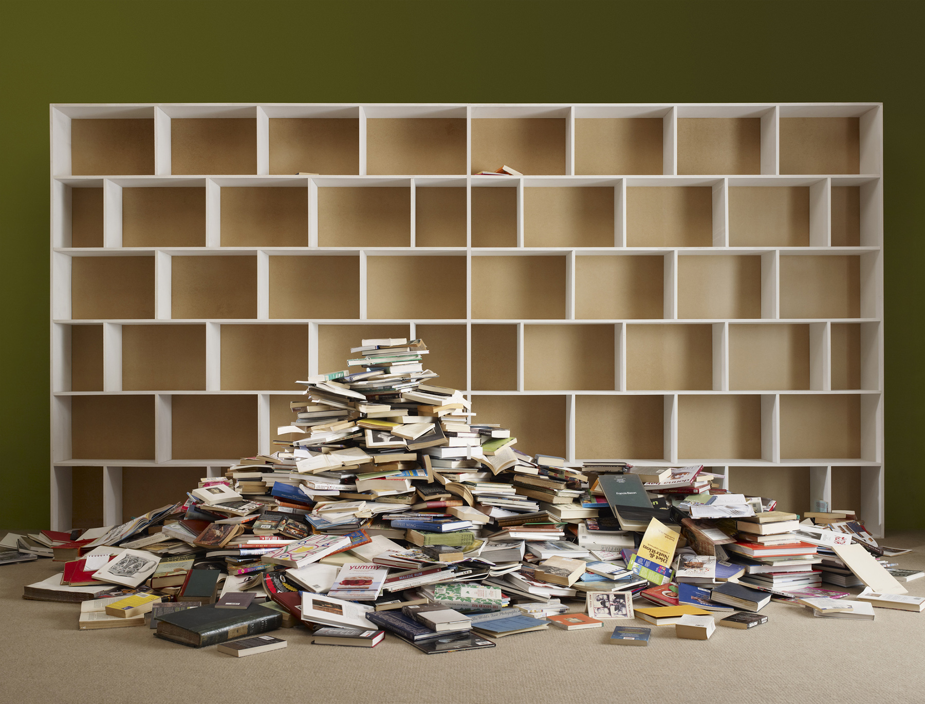 Giant pile of books by an empty bookshelf