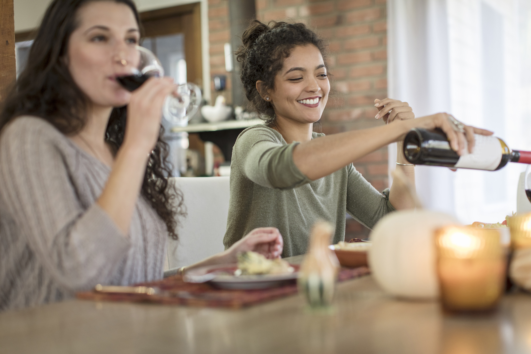 Women drinking red wine at table