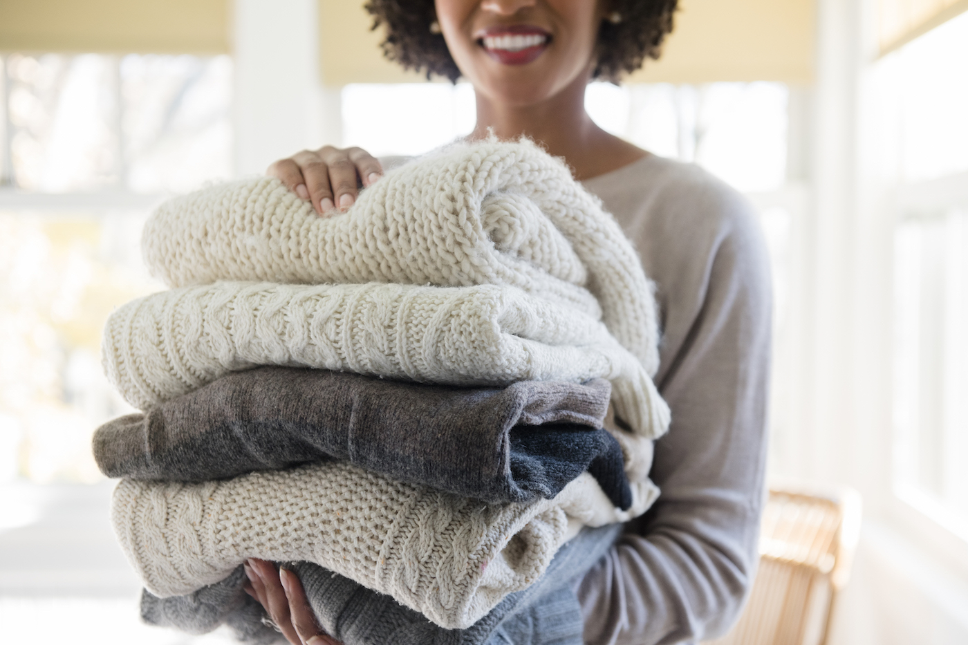 woman carrying stack of folded sweaters with pilling