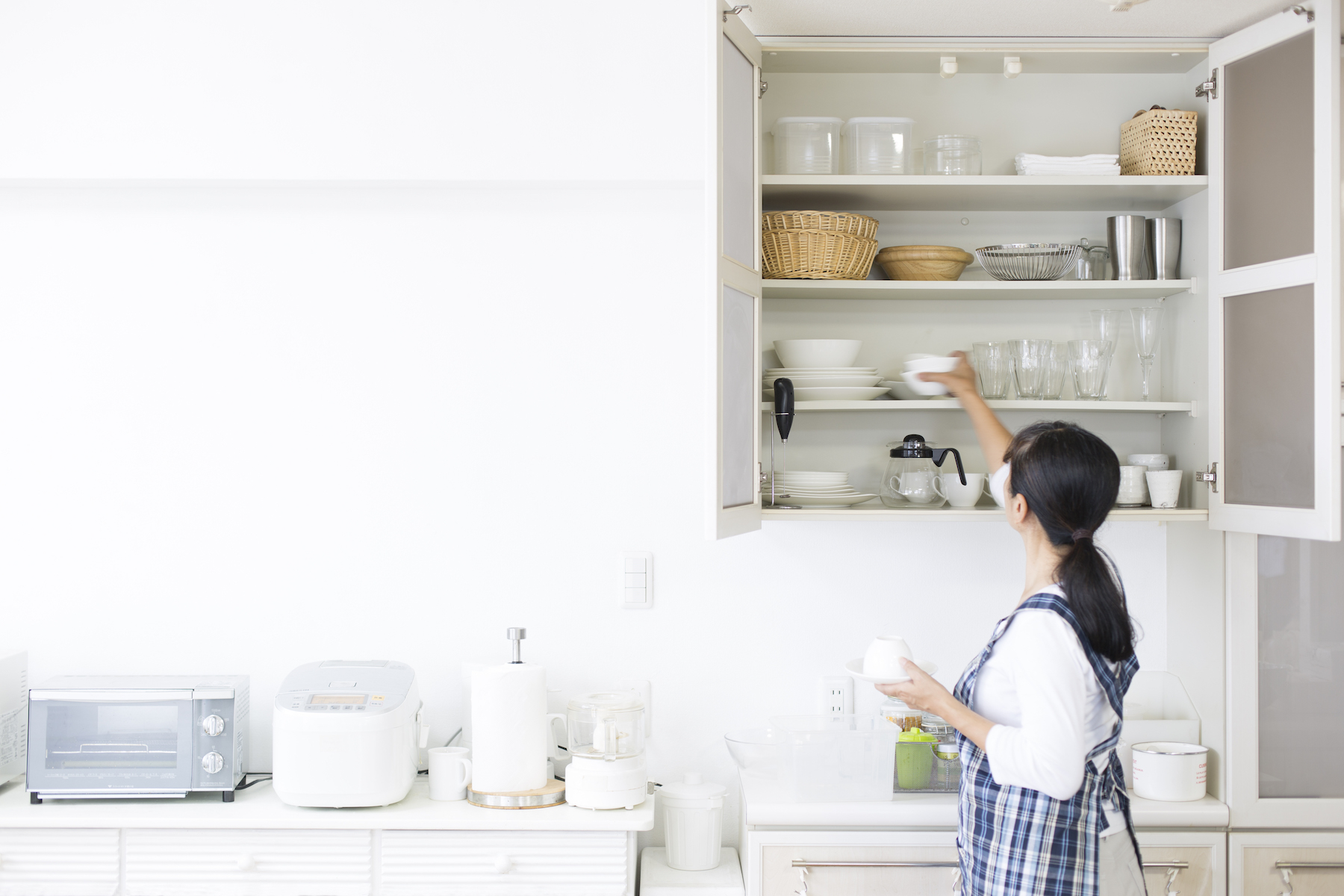 Clutter Stress Connection Research, woman tidying up in kitchen