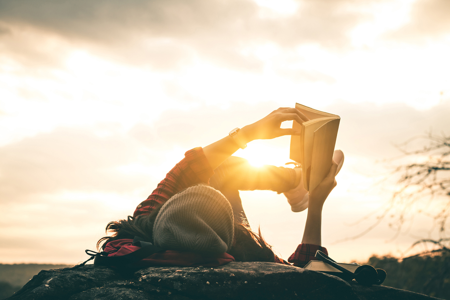 Woman reading a book on her back outside at sunset