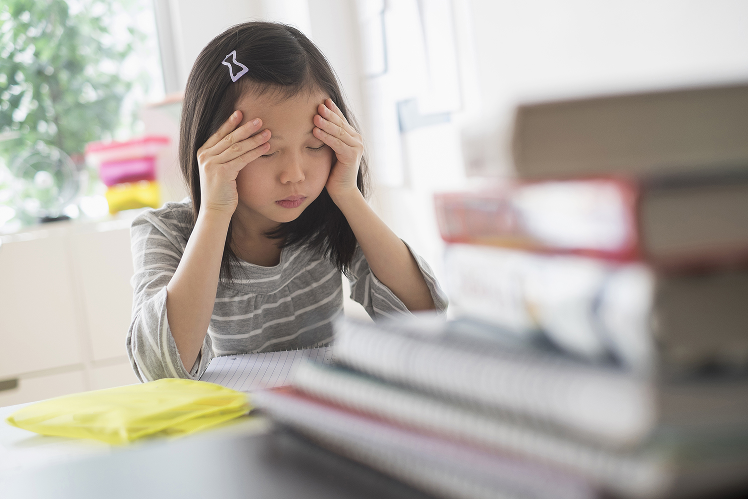 Young girl with headache and schoolbooks