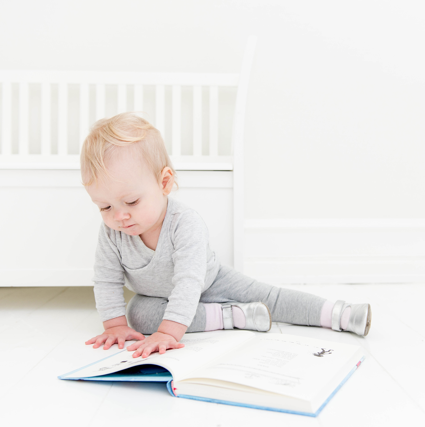 Baby looking at large book