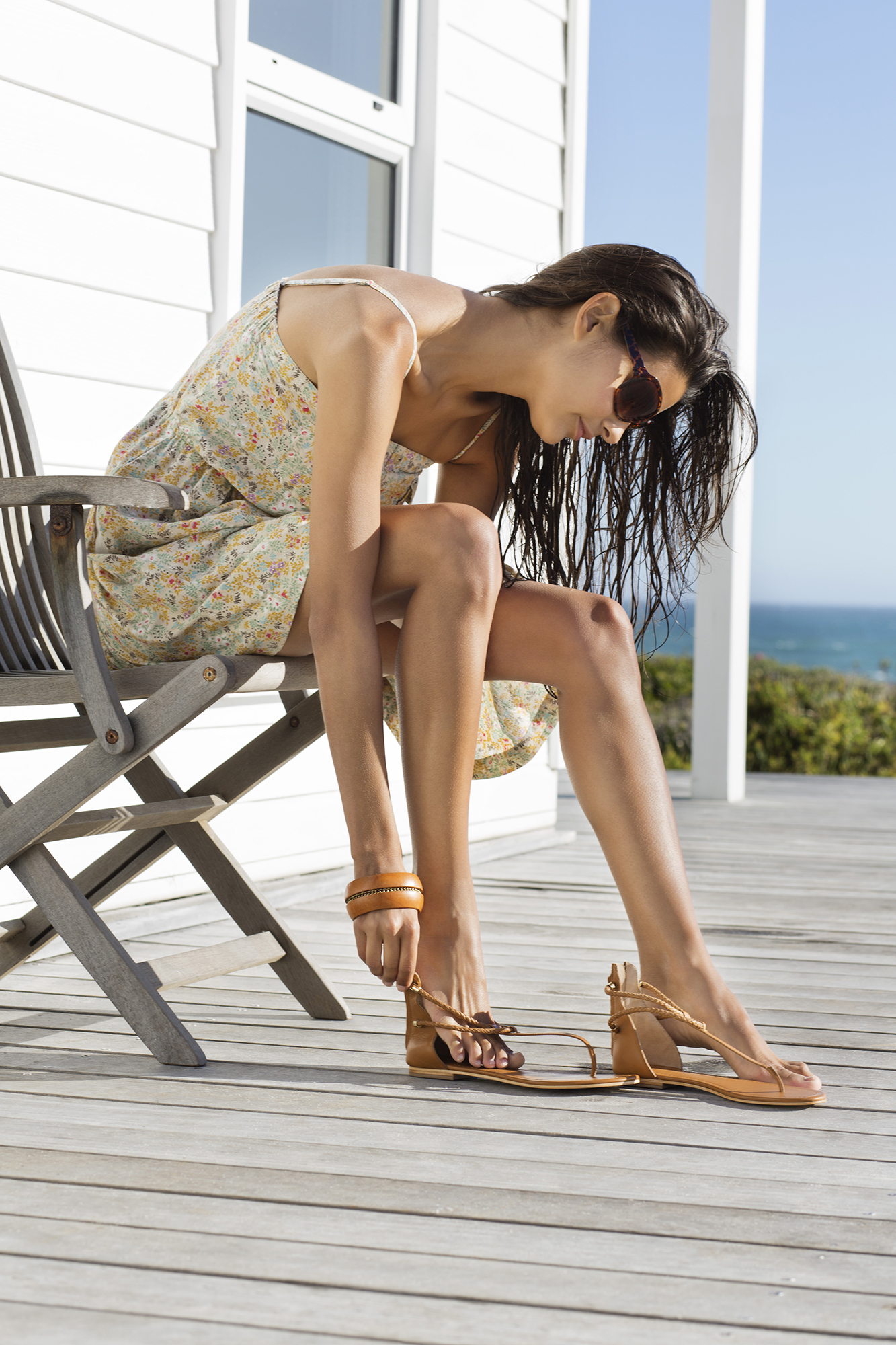 Woman on beach house porch putting on sandals