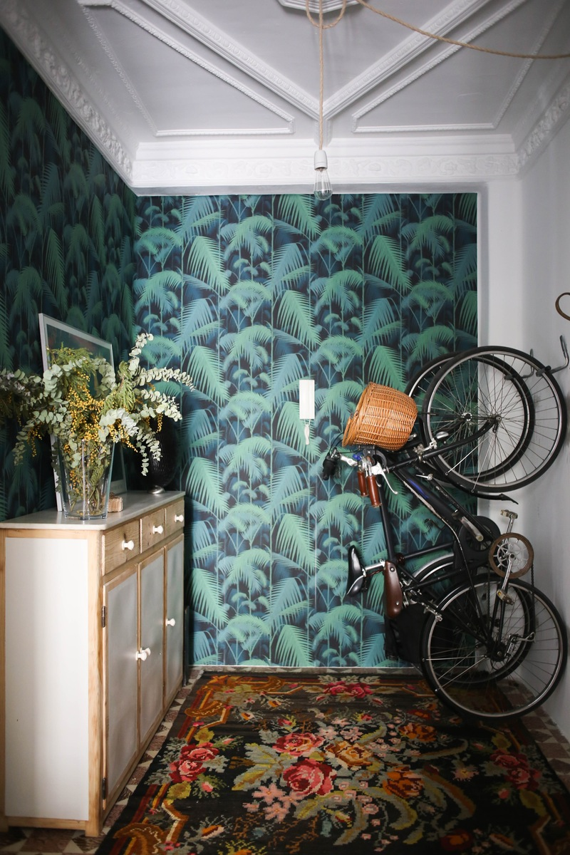 Bicycle in entryway hanging from hooks