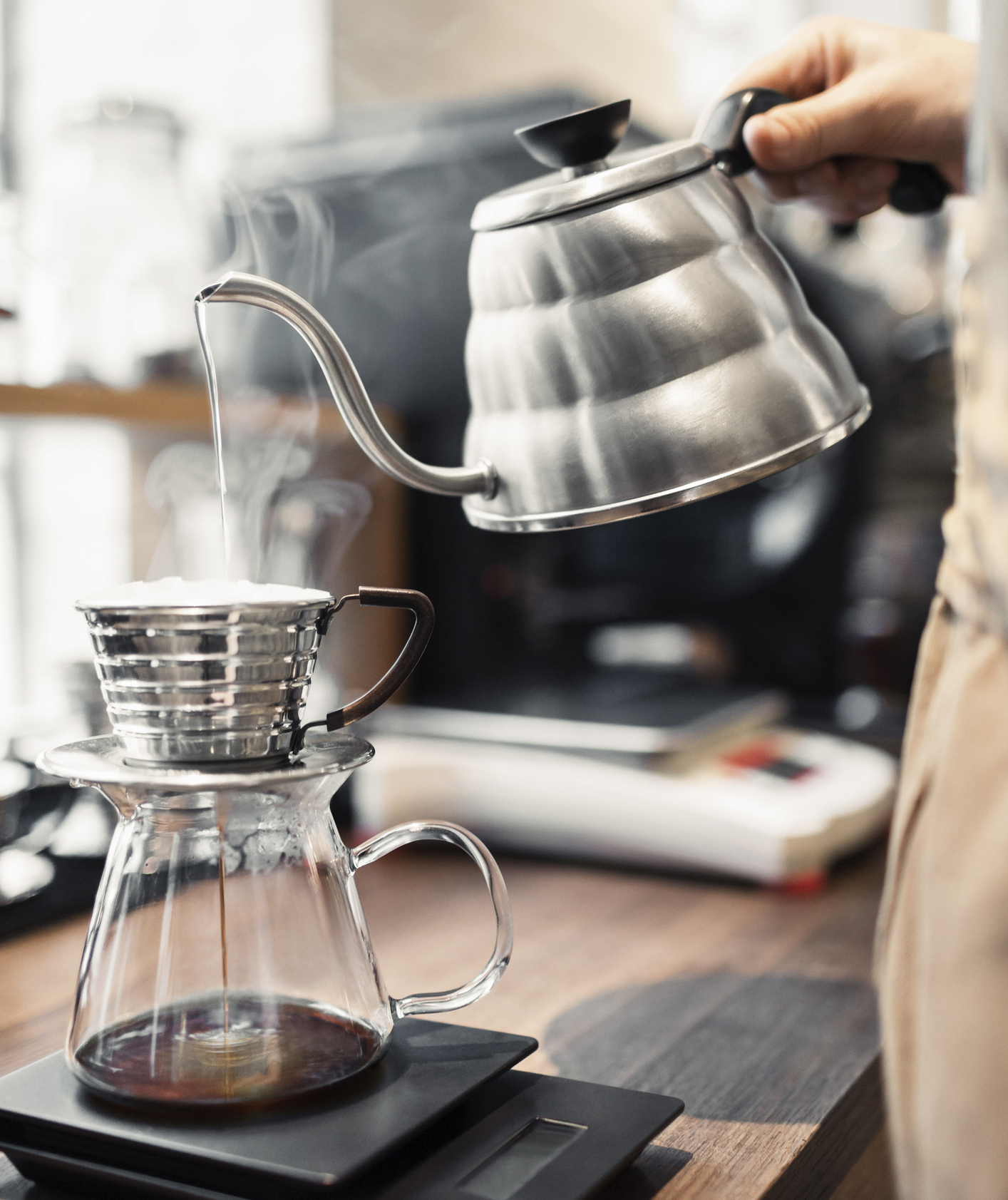 Barista pouring water over coffee