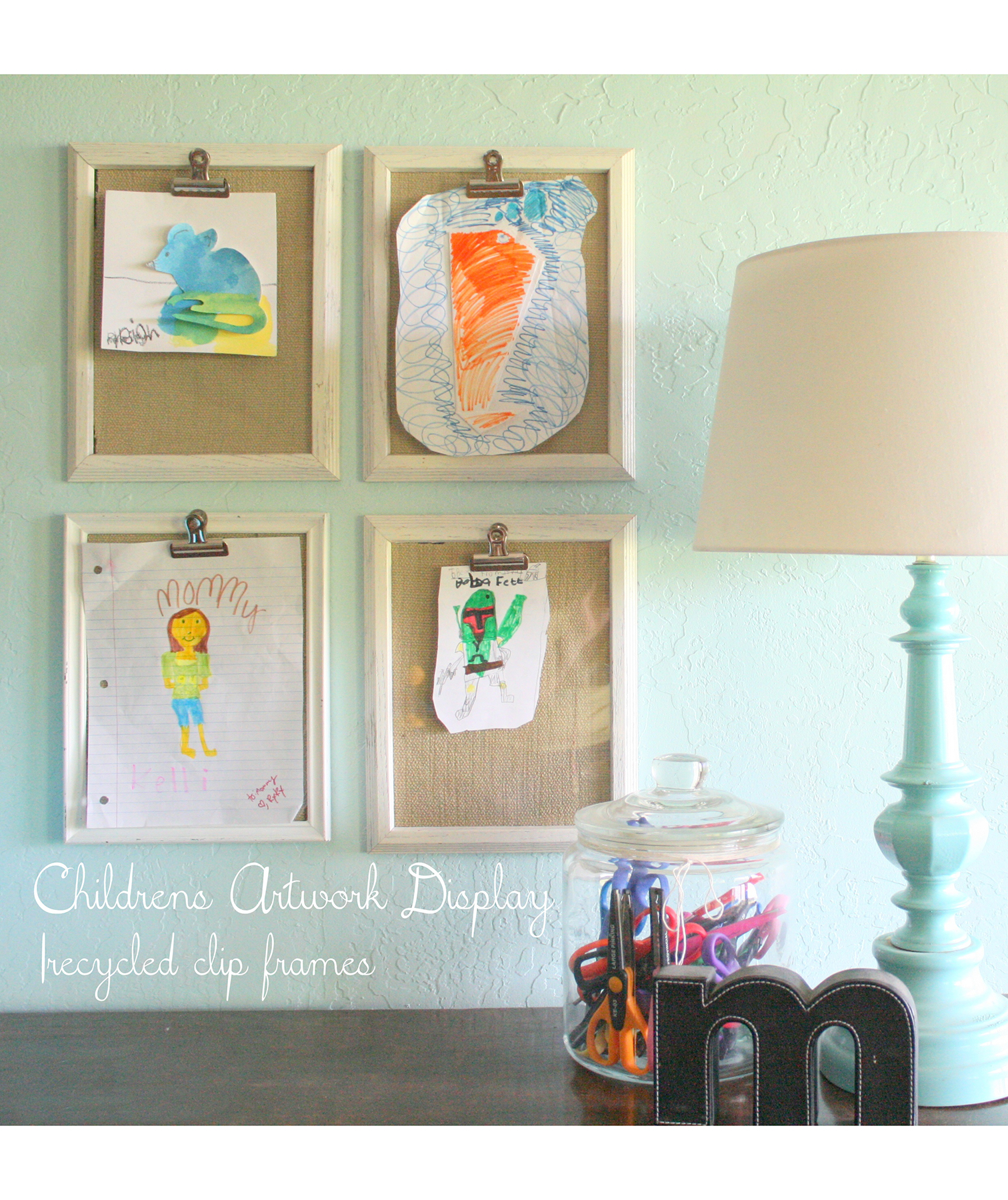 Kids' art on clipboards on wall