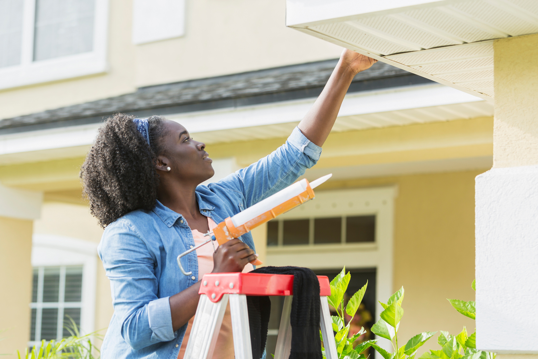 Woman fixing leak as a fall home improvement project