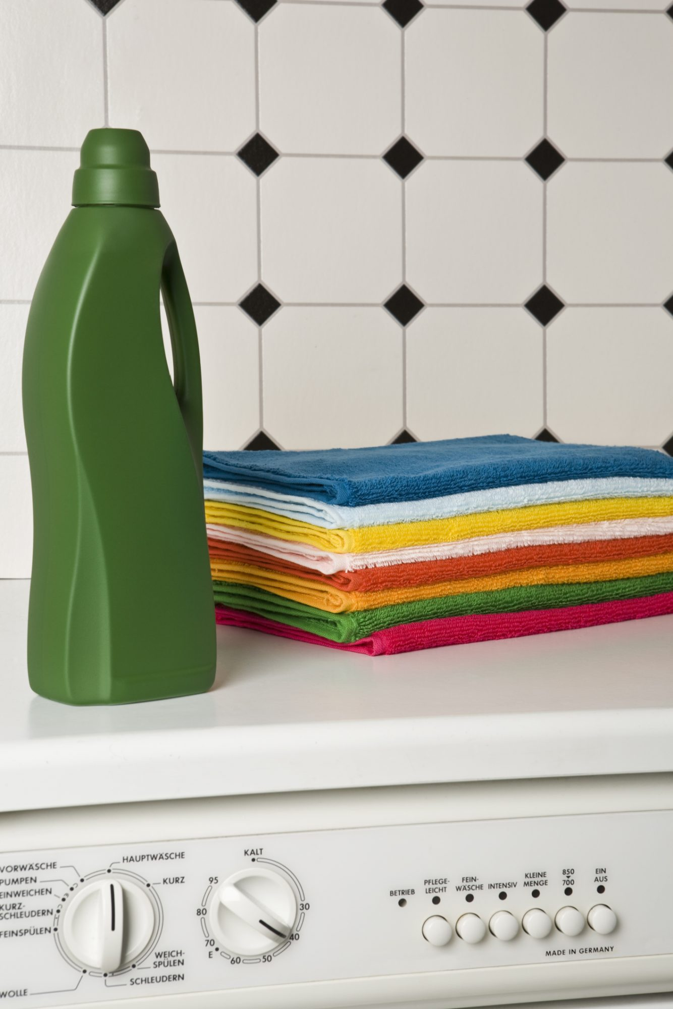 Colorful towels and green detergent bottle on top of washer