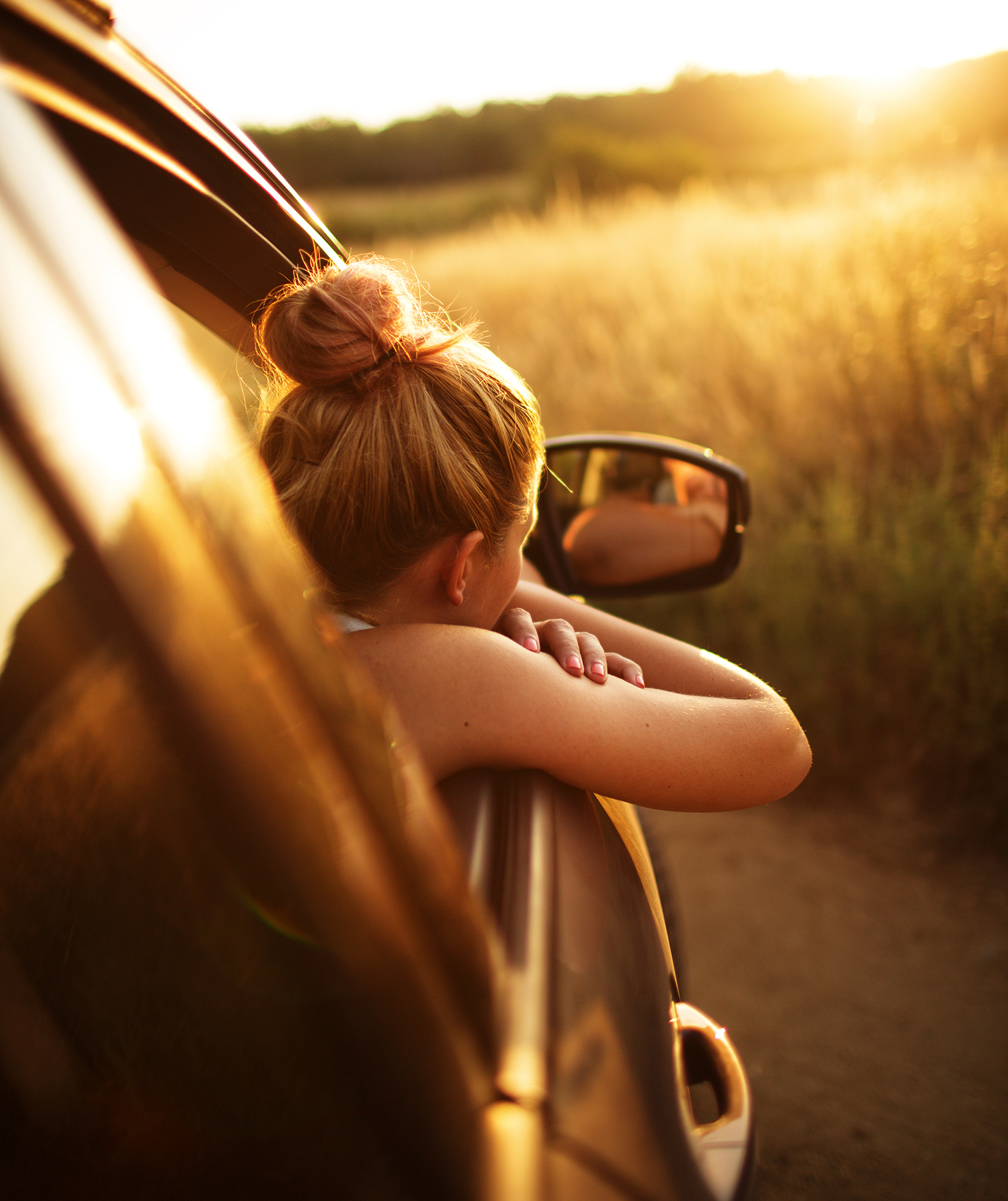 Girl leaning out of car window on road trip
