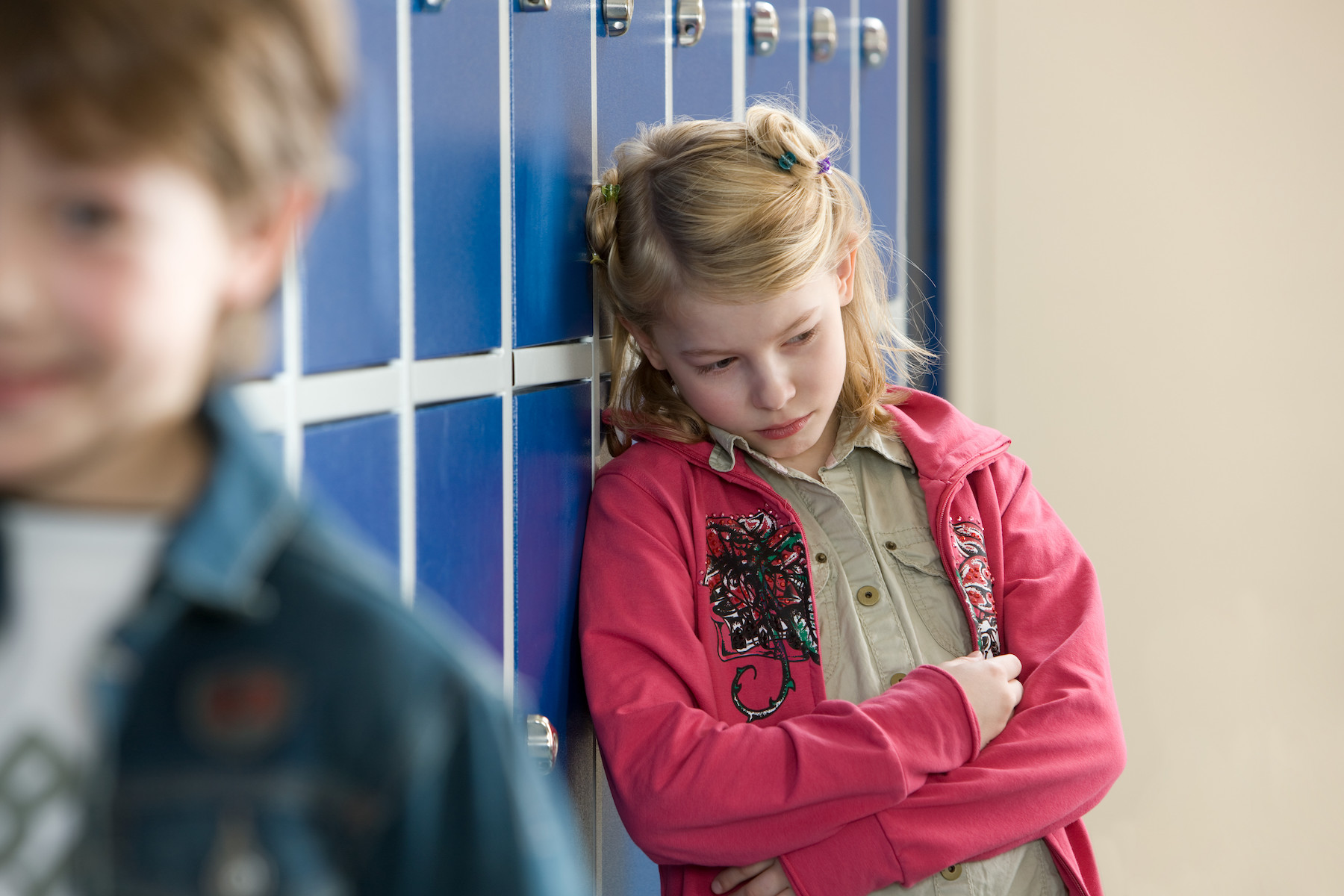 Girl in pink jacket leaning against locker