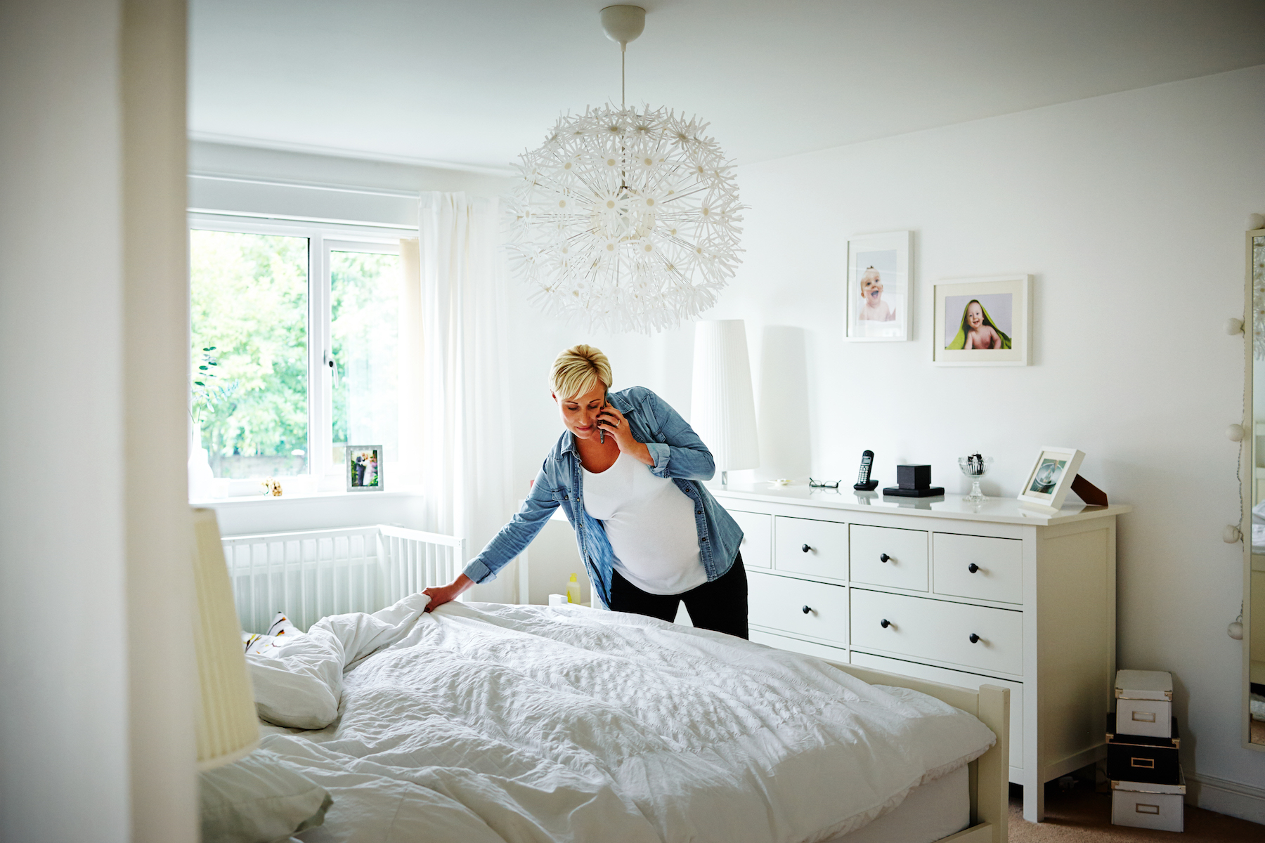 Woman making bed while cleaning bedroom