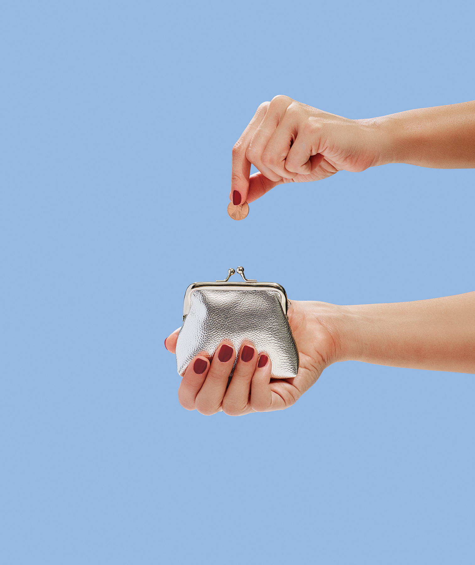 Hand putting penny in coin purse
