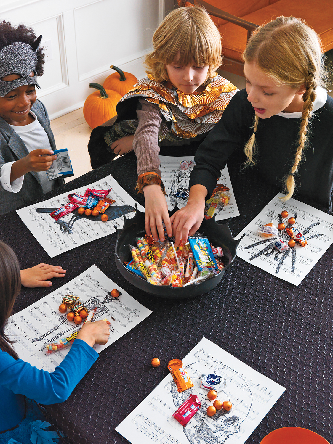 Children reaching into a bowl of candy at a Halloween party