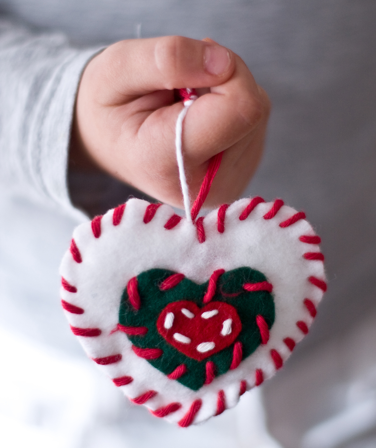 Child with homemade heart ornament