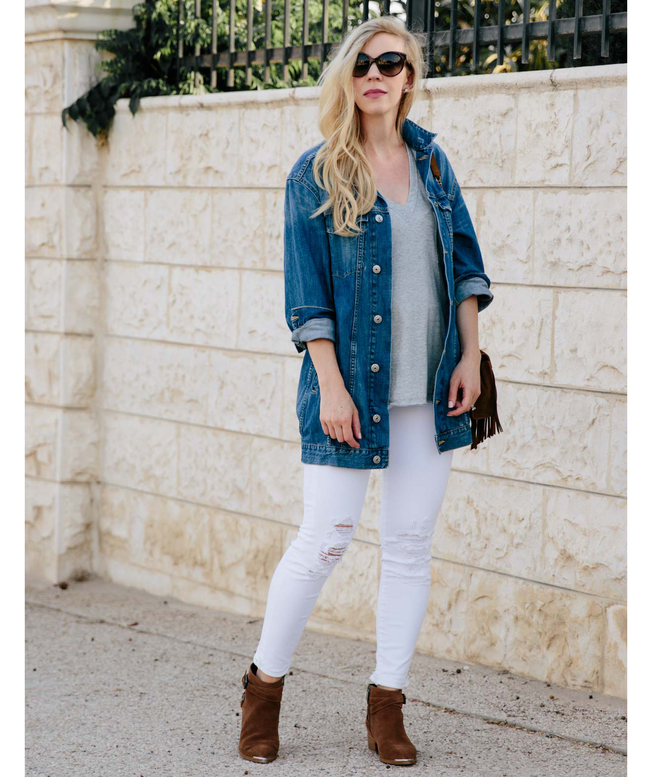 Woman wearing oversized jean jacket with white jeans