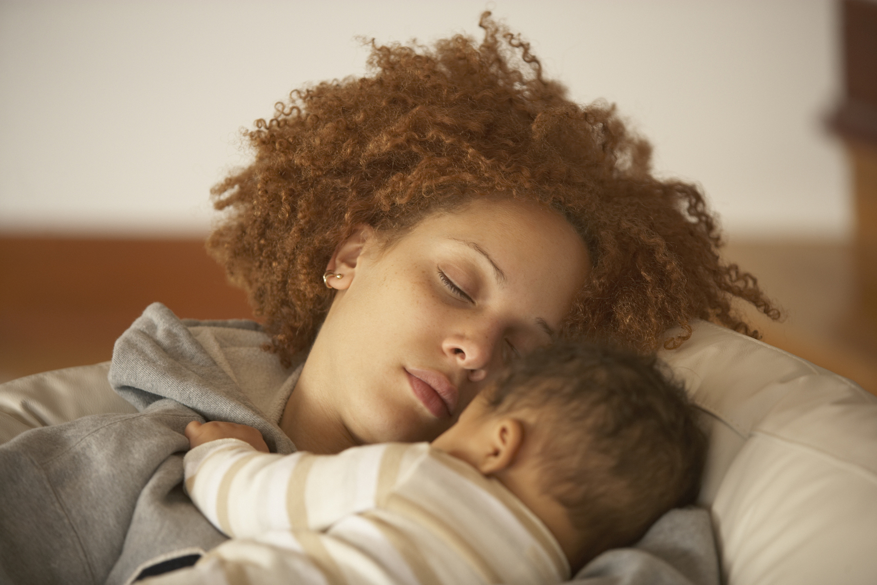 Mom sleeping with baby on shoulder