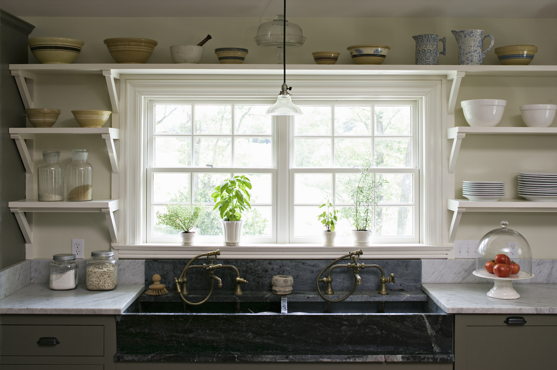Organized Farmhouse kitchen with open shelving and farmhouse double sink, large window