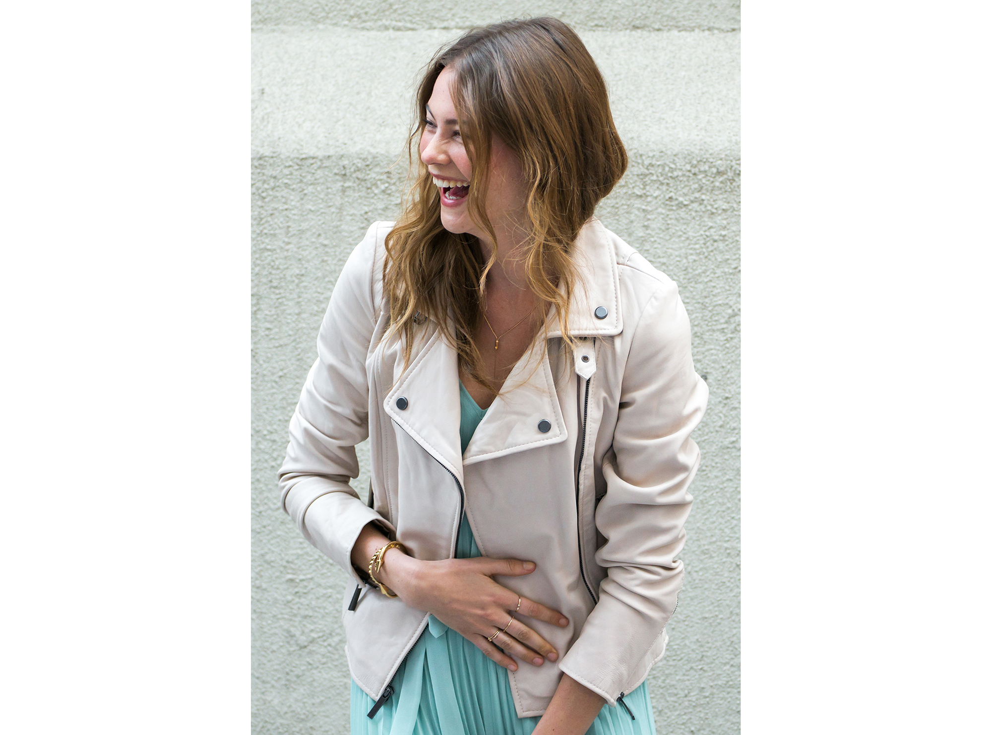 Woman wearing light-colored moto jacket with dress