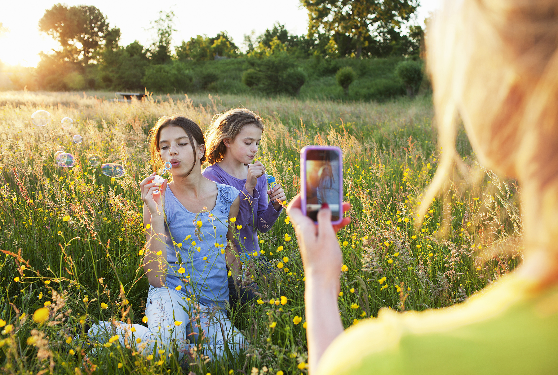 Woman taking photo of two girls in field blowing bubbles
