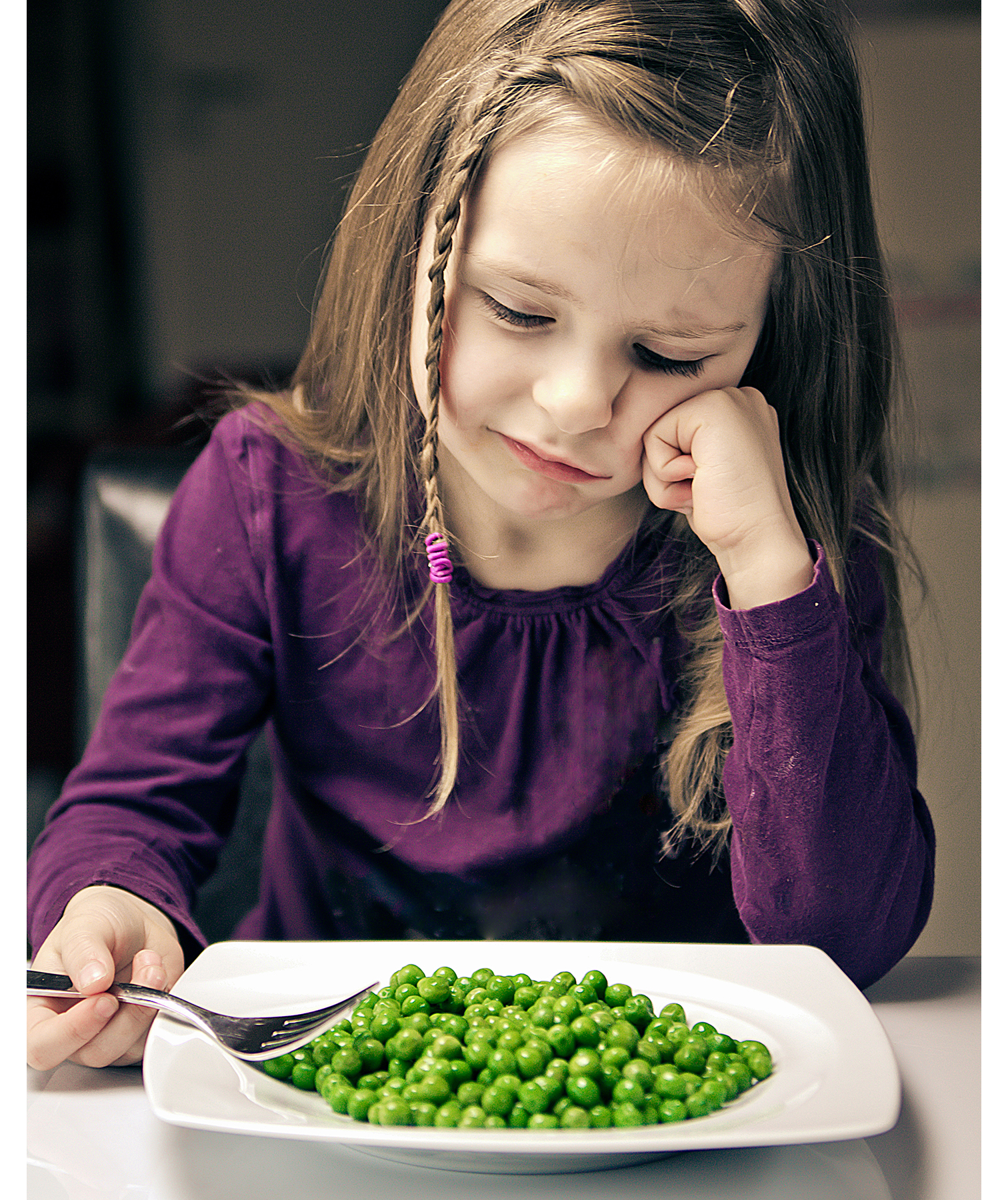 Girl upset about eating peas