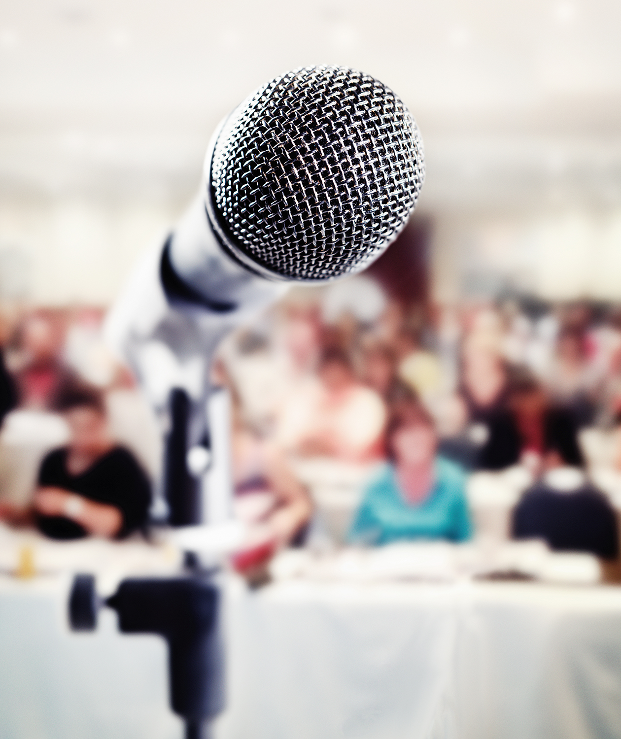 Microphone in front of audience seated at tables