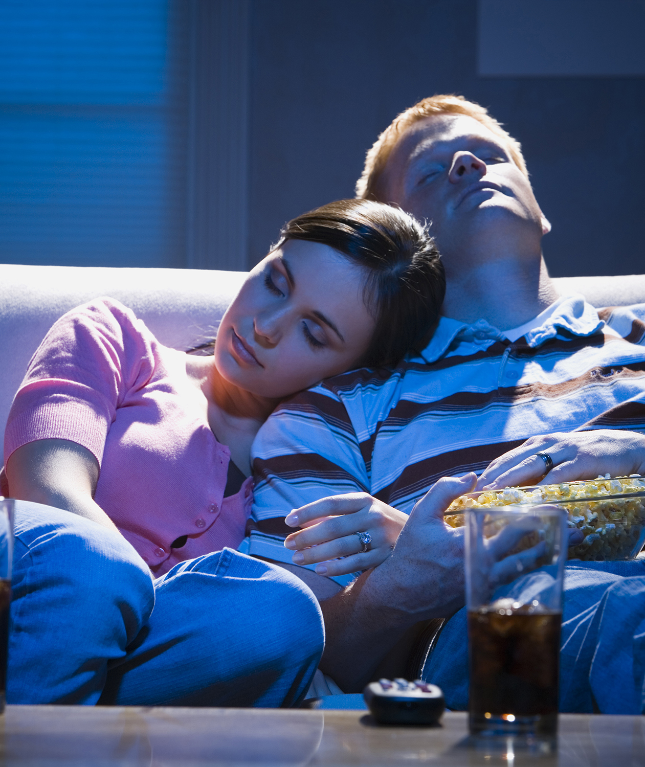 Couple falling asleep on couch watching TV