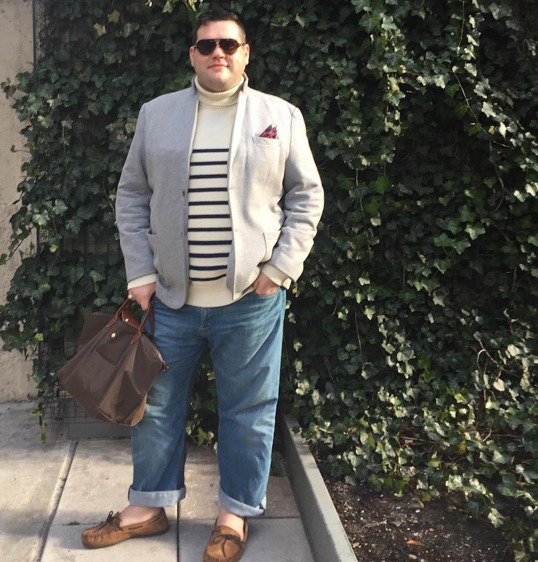 Ryan Dziadul with striped sweater, jacket, jeans, pocket square