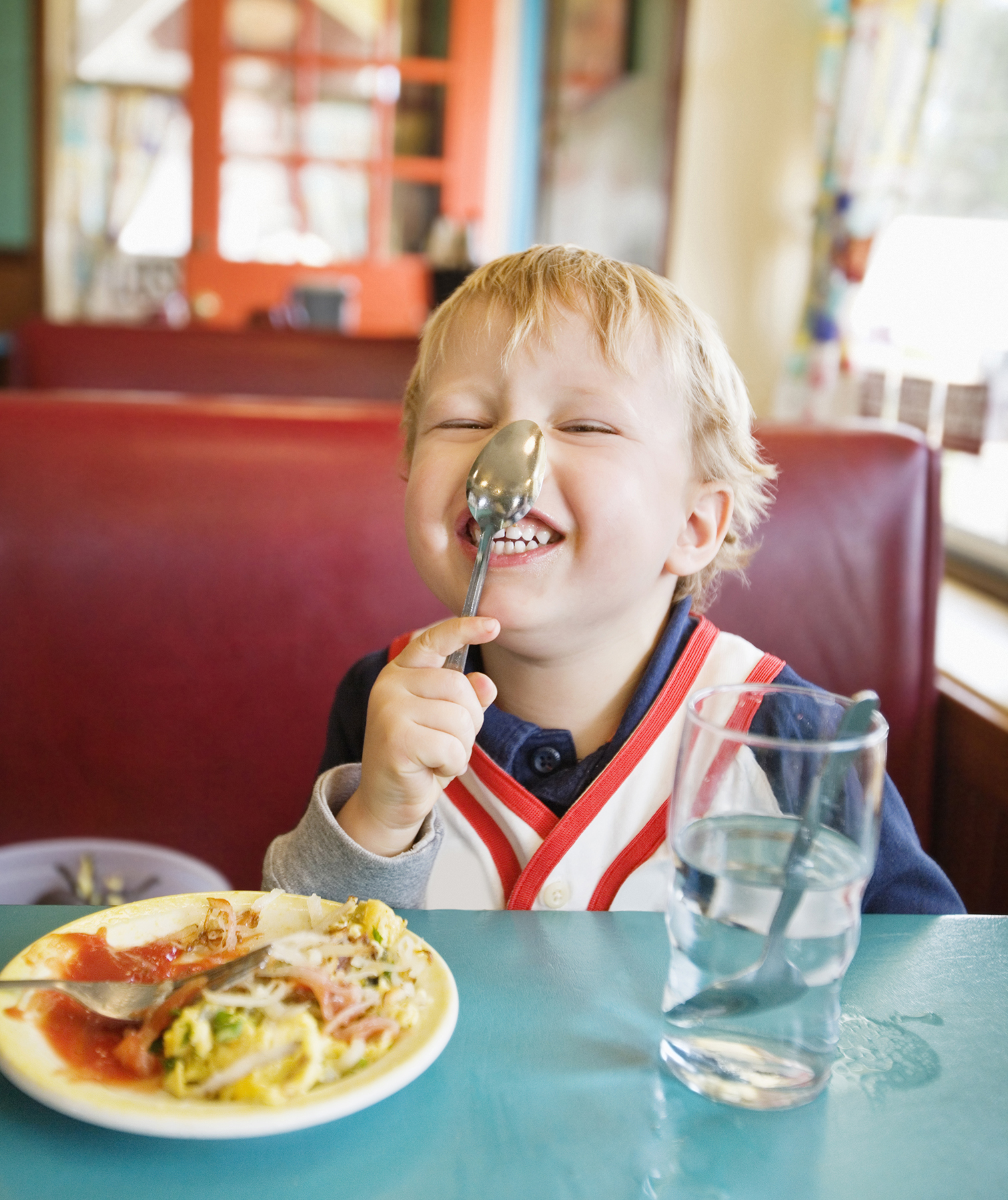 Toddler with spoon on his nose at restaurant