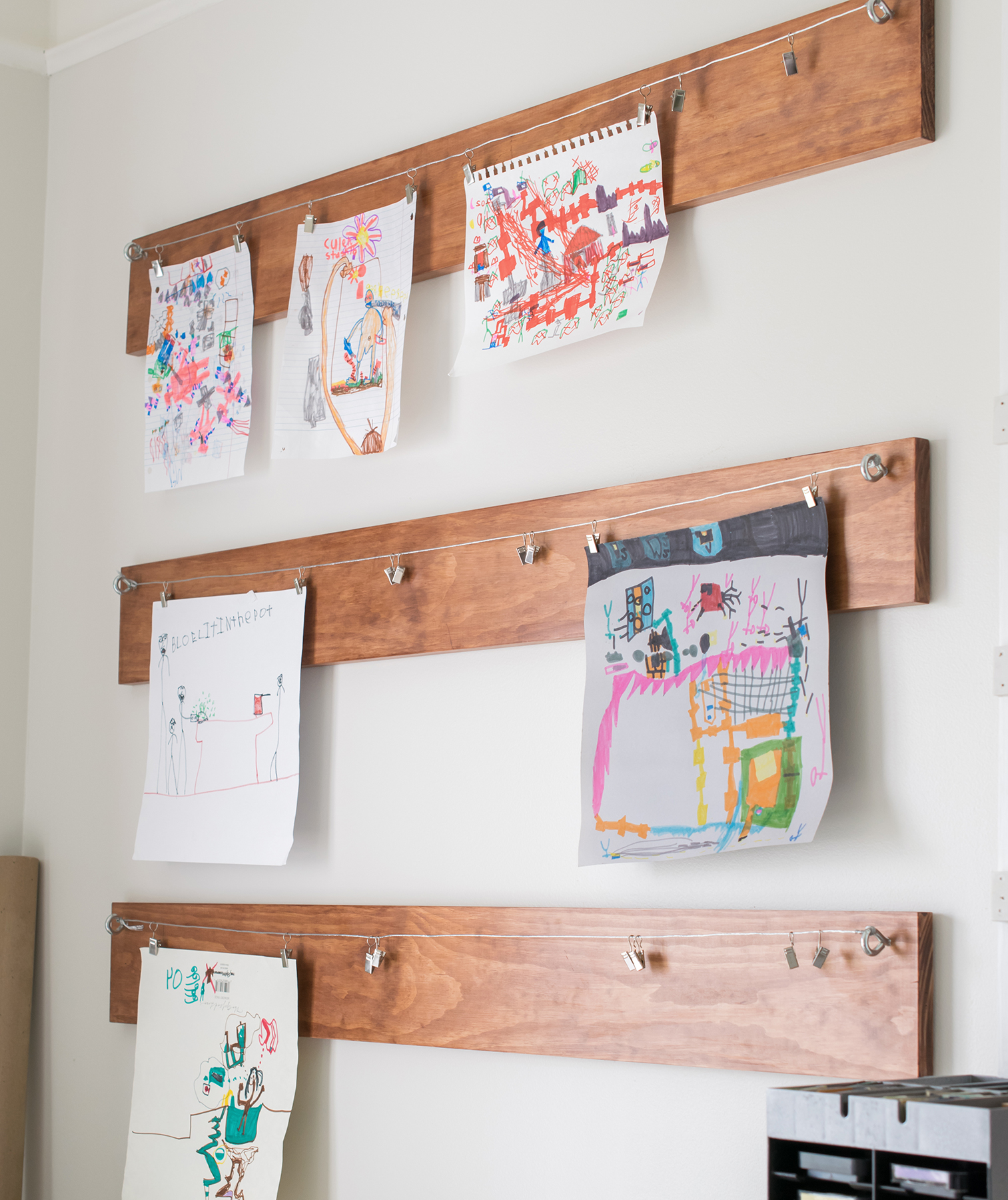 Kids' art hanging from wire on wood boards