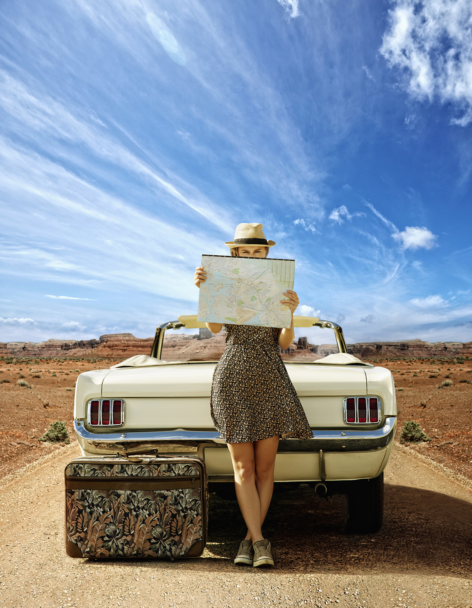 Woman with convertible reading map on remote road