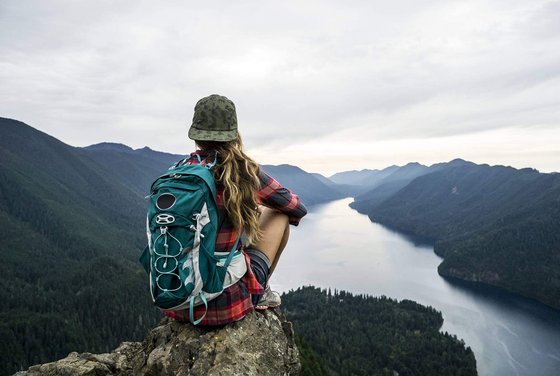 Woman hiker sitting on rock with river view