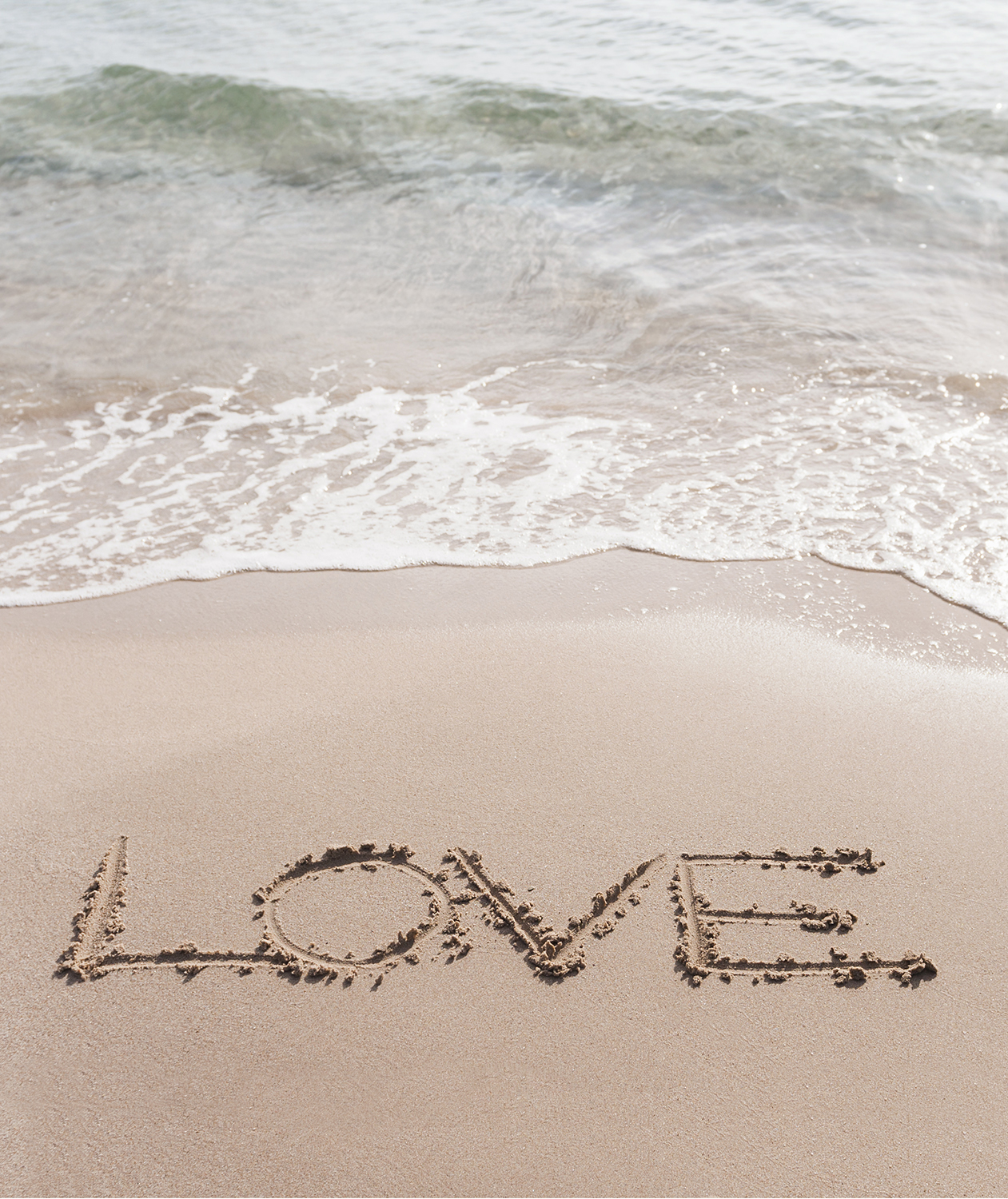 Love written in the sand on beach